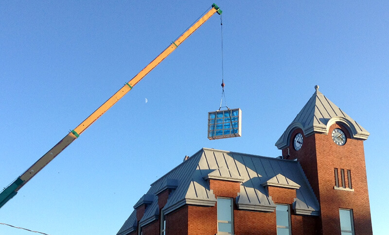 skylight hoisted onto roof of harriston old post office