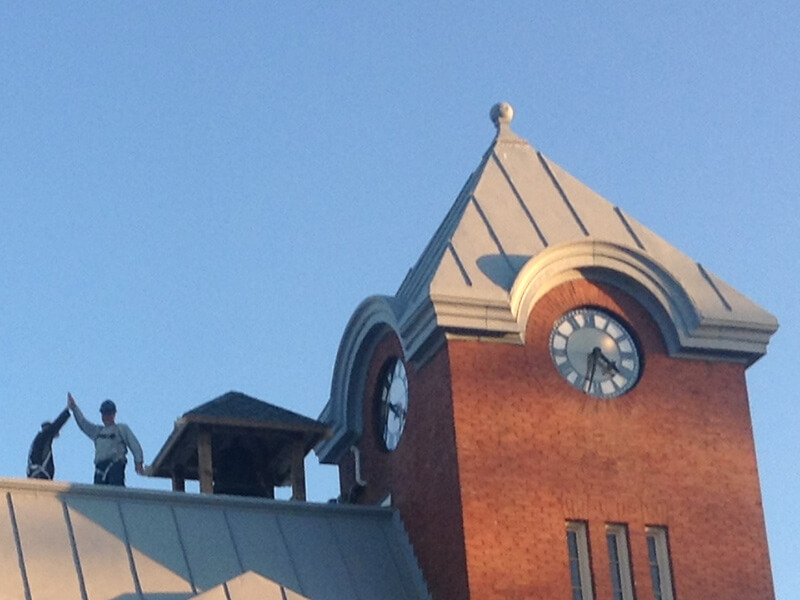 contractors high five on roof of harriston old post office