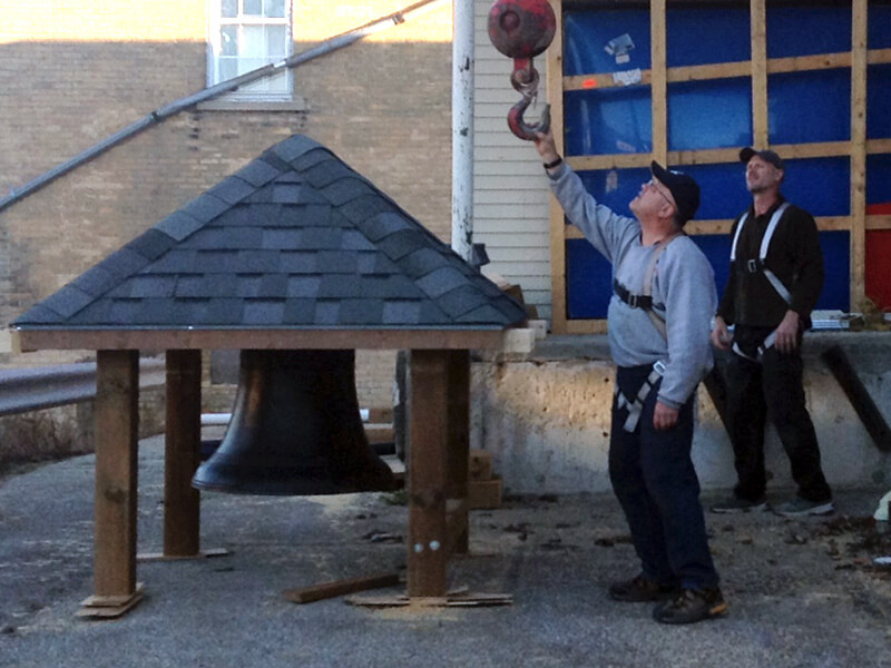 contractors attaching bell to crane at harriston post office